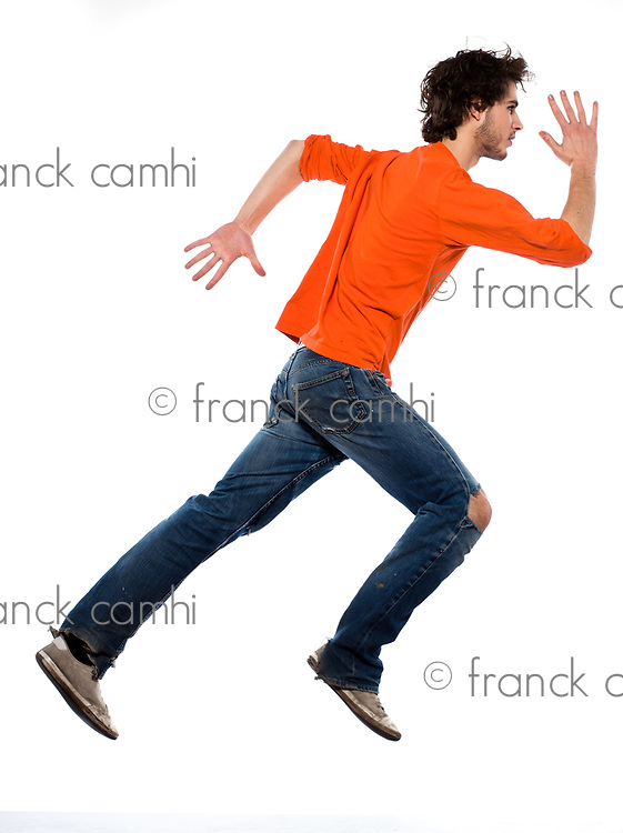 one caucasian young man running profile full length in studio on white background