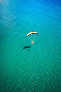 Aerial view of powered paraglider flying low over clear ocean