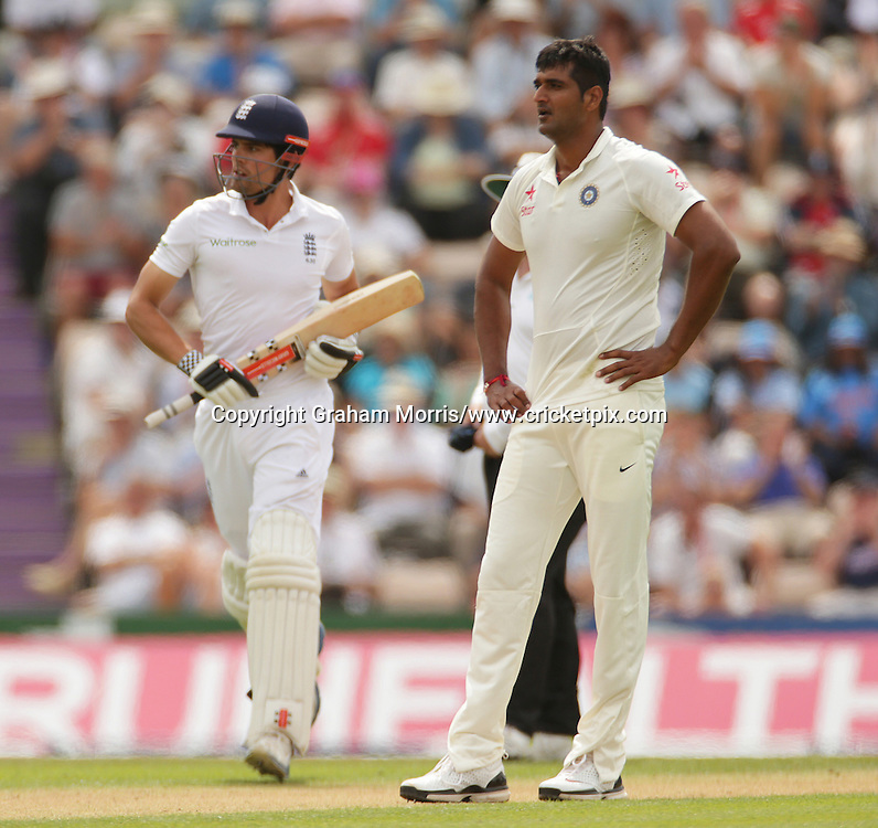 Alastair Cook runs past frustrated bowler Pankaj Singh during the third Investec Test Match between England and India at the Ageas Bowl, Southampton. Photo: Graham Morris/www.cricketpix.com (Tel: +44 (0)20 8969 4192; Email: graham@cricketpix.com) 27/07/14