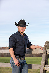 hot cowboy by a wooden fence on a ranch