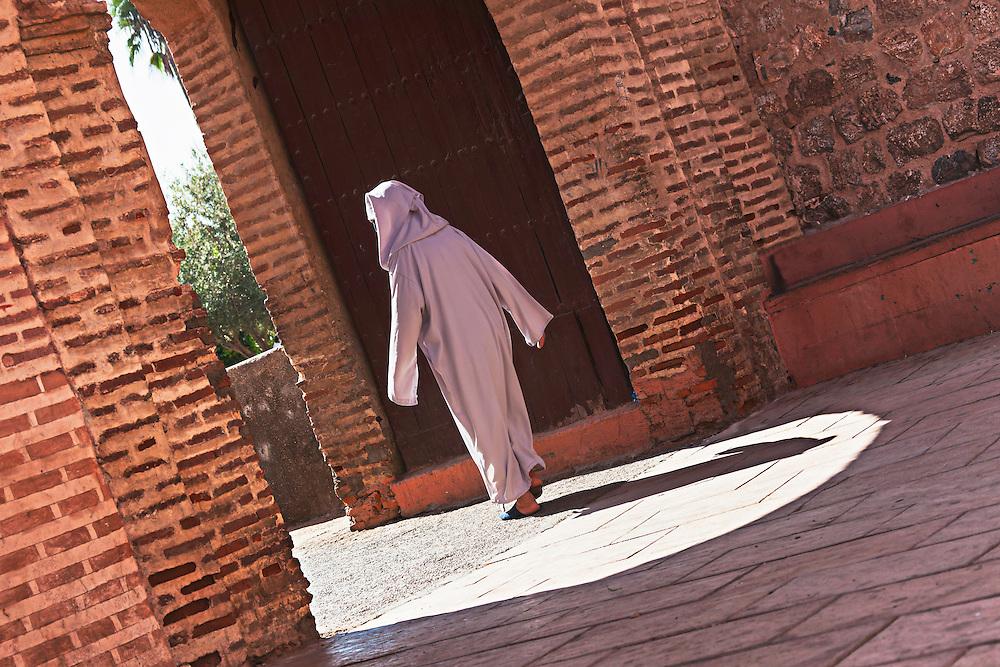 Woman walking through a gate at the Koutoubia mosque, Marrakech, Morocco.