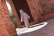 Woman walking through a gate at the Koutoubia mosque, Marrakech, Morocco.