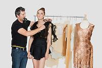 Mature male fashion designer adjusting dress on model in design studio