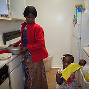 "Atlanta, Georgia/Central Africa Republic Refugee/Nestorine Lakas, 27, does dishes at her apartment in Atlanta, Georgia with her 3-year-old daughter Carol  at their apartment in Atlanta. Nestorine arrived in the U.S. in 2010 with her two young children from the Central African Republic. Her oldest son, who is now 7 years old, suffers from severe cerebral palsy and requires a wheelchair and specialized healthcare. At the IRC in Atlanta, Nestorine is part of the Temporary Assistance for Needy Families (TANF) program where she is learning English, job skills and basic computer literacy so she can support her family as a single mom and learn how to manage her son's health needs. Unfortunately the father of Nestorine's children was not able to come to the U.S. with her, so she cares for her children and dreams of reuniting with him someday. Nestorine believes what makes her successful is ?working hard and overcoming challenges?. ""There was a war in my country and I fled to Cameroon. I was pregnant with my older son and gave birth along the way. When I fled I was alone. When I got to the camp I found my husbands name on a sign at the camp and we were reunited. My daughter Carol was born in Cameroon."" Because of her son's disability Nestorine got a humanitarian visa with the help of UNHCR. ""I am very happy to be here because they helped me a lot with my child. If I had stayed in CAR there isn't the healthcare that I have here. I am very thankful. The reason my child is still alive because I came as a refugee. Maybe the child would not have had any hope to walk. I hope one day he might walk.""."