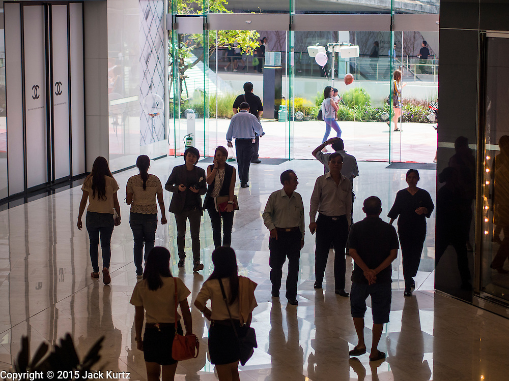 "27 MARCH 2015 - BANGKOK, THAILAND: Shoppers walk into ""EmQuartier,"" a new shopping mall in Bangkok.  ""EmQuartier"" is across Sukhumvit Rd from Emporium. Both malls have the same corporate owner, The Mall Group, which reportedly spent 20Billion Thai Baht (about $600 million US) on the new mall and renovating the existing Emporium. EmQuartier and Emporium have about 450,000 square meters of retail, several hotels, numerous restaurants, movie theaters and the largest man made waterfall in Southeast Asia. EmQuartier celebrated its grand opening Friday, March 27.   PHOTO BY JACK KURTZ"