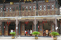 Men playing the  Chinese game Mahjong in a temple in China (wide).