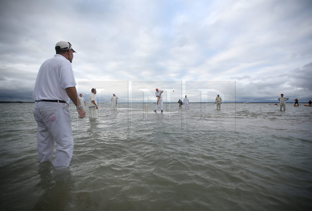 © Licensed to London News Pictures. 31/08/2015. Southampton, UK. Members of the The Island Sailing Club and The Royal Southern Yacht Club take part in the annual Bramble Bank cricket match. The yearly fixture takes place on a small sandbank which is briefly exposed at low tide in the middle of the Solent waterway. Photo credit : Peter Macdiarmid/LNP