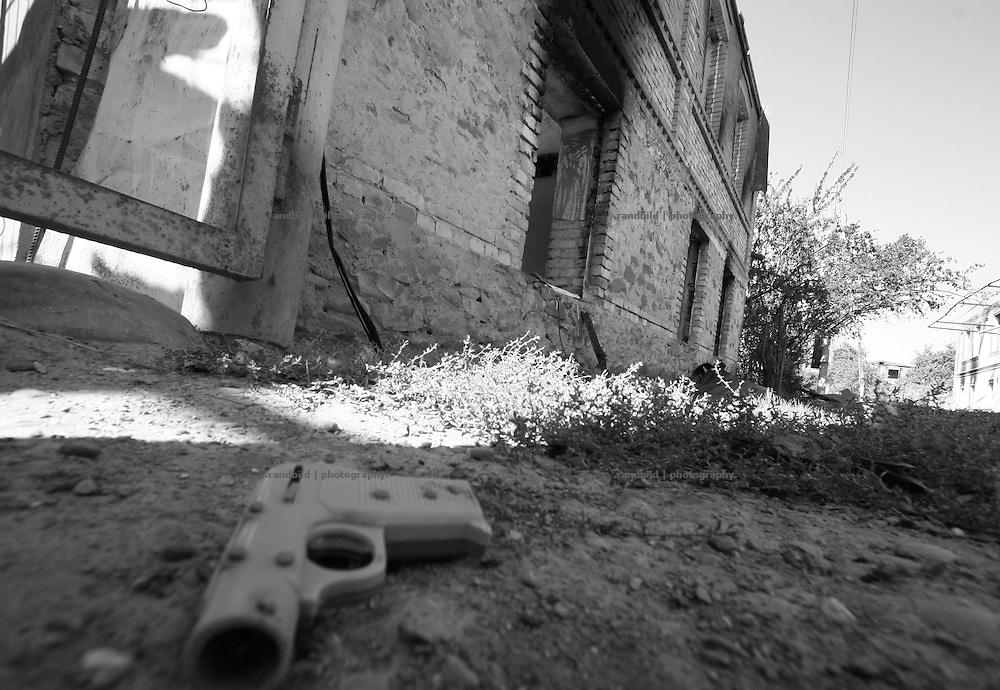 A toy pistol lies on the ground in front of a burnt out house in Ergneti, located in the so called bufferzone between Gori and Tskhinvali, few days after the withdrawal of the russian forces from the area. The bufferzone was etablished after a short war in August 2008 as the georgian army assulted South Ossetia to overthrow the local separatist government.