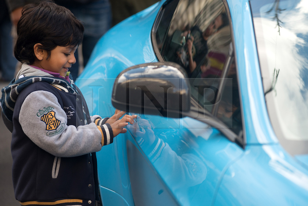 © Licensed to London News Pictures.02/11/2013. London, UK. A boy admires cars at the Regent Street Motor Show that is the largest free motor show in the UK. More then 300 vehicles are displayed, from classic automobiles of the Victorian age right up to the very latest 'super' cars of today. Photo credit : Peter Kollanyi/LNP
