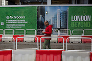 A red and green construction hoarding with a pedestrian walking past wearing identical colours, on 16th February 2017, in the City of London, England.