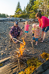 A young family enjoys a camp fire on East Gosling Island in Casco Bay, Harpswell, Maine.