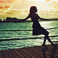 Photo of a female silhouette with a river in the background and orange sky with the sun shinning through the clouds, the image has a texture to complement the retro feel to it.