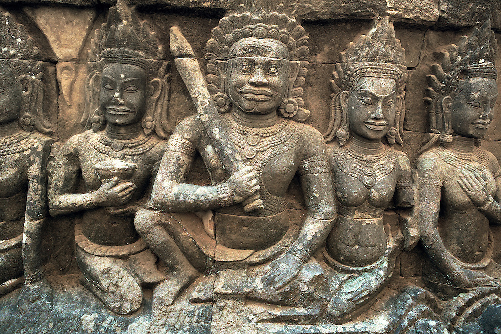 Angkor Thom: reliefs of the king ( Jayavarman VII, 12th century AD) and deities under the Terrace of the Leper King. Seated posture with right knee upraised is unusual in Khmer art.  Each face shows a calm smile.  Elaborate headdresses, necklaces, and bracelets.