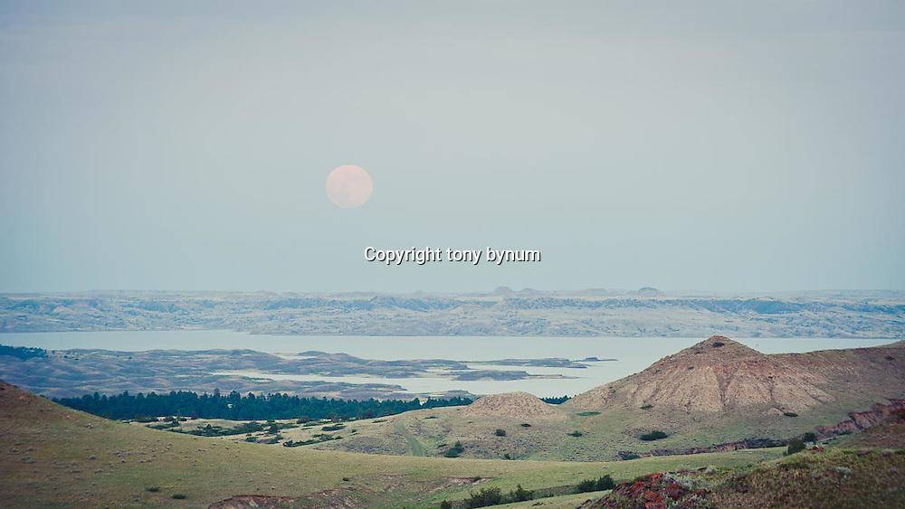 full moon rising over fort peck lake, cmr