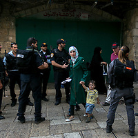 A Palestinian woman and her children walks through police officers along the Hagai&nbsp;Street&nbsp;in Jerusalem's Old City  on after the two attacks, the street turned into a security area, with about 10 checkpoints and hundreds of police posted along it. Most of the Palestinian merchants closed their stores, waiting for the rage to pass.<br />
