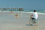 Man on bicycle on Daytona Beach, Daytona Beach Pier in background. Florida, USA
