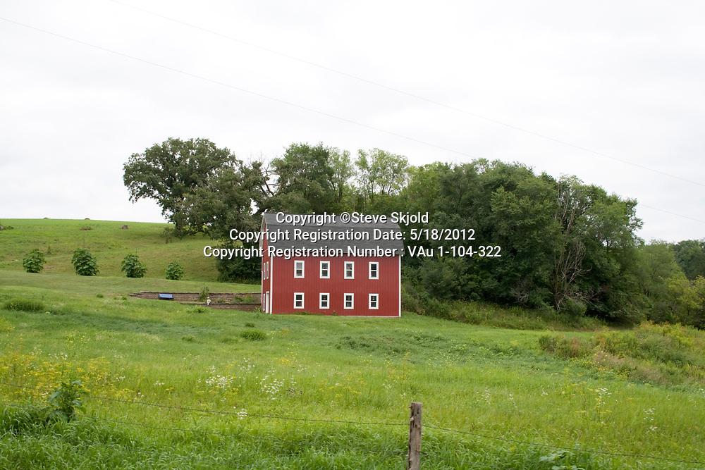 Bright red modern barn or home seemingly all alone in farm field. Lanesboro Minnesota MN USA