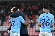 Manchester City manager Pep Guardiola hugs Raheem Sterling (7) of Manchester City ignoring goalscorer Riyad Mahrez (26) of Manchester City at full time after a 1-0 win over Bournemouth during the Premier League match between Bournemouth and Manchester City at the Vitality Stadium, Bournemouth, England on 2 March 2019.