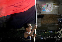A boy supporter of Nicaraguan presidential candidate Daniel Ortega of the Sandinista National Liberation Front (FSLN) run carring the party flag in Managua, Nicaragua, Thursday, Nov. 2, 2006. In the back ground ia a poster with Daniel Ortega's picture. (AP Photo/Cristobal Herrera)..