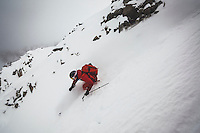 Christopher Smith backcountry skiing on a stormy day in Wolverine Cirque, Wasatch Mountains, Utah.