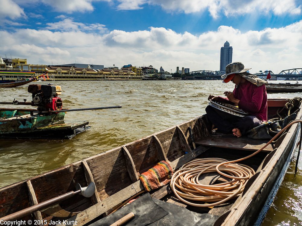 14 OCTOBER 2015 - BANGKOK, THAILAND: A spotter for saleable objects brought up from the river bottom while the diver he works with is in the Chao Phraya River in Bangkok. Divers work in two man teams on small boats in the Chao Phraya River. One person stays in the boat while the diver scours the river bottom for anything that can be salvaged and resold. The divers usually work close to shore because the center of the river is a busy commercial waterway with passenger boats and commercial freight barges passing up and down the river all day long. The Chao Phraya is a dangerous river to dive in. It's deep, has large tidal fluctuations, is fast flowing and badly polluted. The divers make money only when they sell something.    PHOTO BY JACK KURTZ