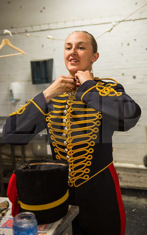 © London News Pictures. 14/07/2015.  Gunner Christie Farren makes the finishing touches to her uniform.<br />  . More usually associated with the ceremonial gun salutes and musical rides with their 13lb guns, they took on the role of both mounted and dismounted guard at the entrance of Horse Guards. This year, for the first time, they are using Knightsbridge Barracks, the home of the Household Cavalry Mounted Regiment, for the period of their duty, as opposed to Wellington Barracks, which they have used in previous years.  Photo credit: Sergeant Rupert Frere/LNP