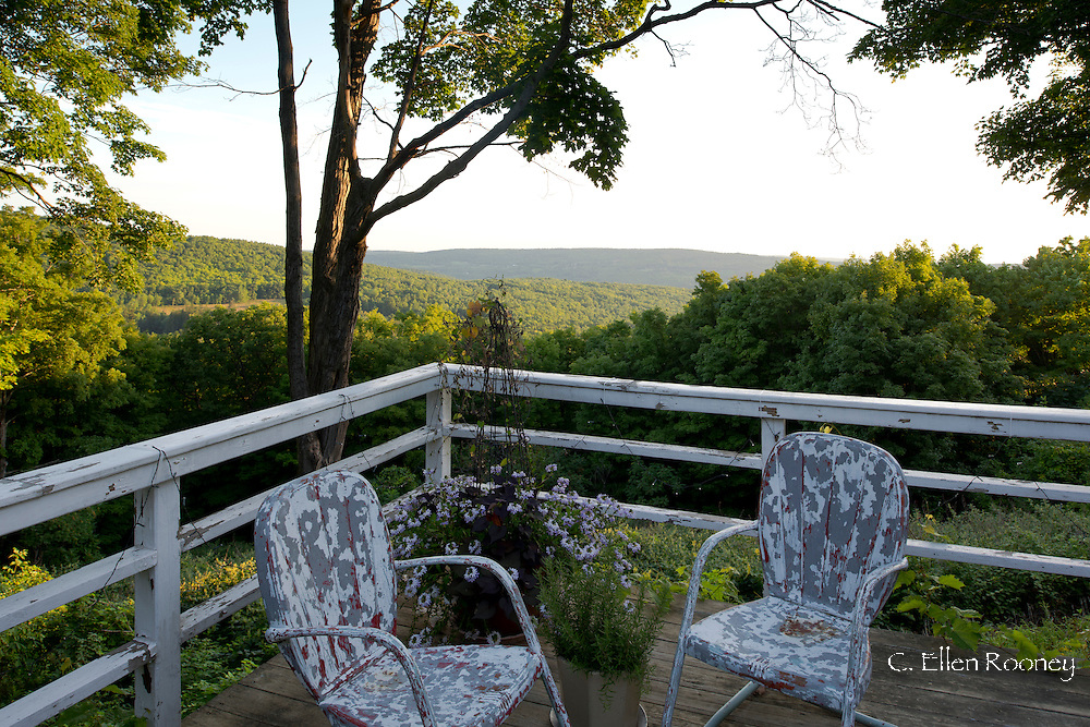 Vintage American metal chairs on a deck overlooking hills in artist Katherine Bowling's garden in Potter Hollow, New York, U.S.A.