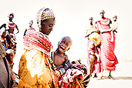 Despite the hardship of a nomadic life in a drought-plagued land, the Rendille people are well known for their beautiful fabrics and brightly coloured beads. Nkoror Galangan (28) is no exception and manages to look like a Rendille Queen as she comforts her sick daughter Diboya. <br /> <br /> Marsabit District, Northern Kenya