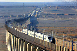 "File photo taken on Nov. 15, 2014 shows a bullet train running on the Lanzhou-Xinjiang high-speed railway, northwest China. ""Building more high-speed railways"" has been a hot topic at the annual sessions of China's provincial legislatures and political advisory bodies intensively held in January. China has the world's largest high-speed rail network, with the total operating length reaching 19,000 km by the end of 2015, about 60 percent of the world's total. The expanding high-speed rail network is offering unprecedented convenience and comfort to travelers, and boosting local development as well. Chinese companies have developed world-leading capabilities in building high-speed railways in extreme natural conditions. High-speed railway routes across China have been designed to suit its varying climate and geographical conditions. The Harbin-Dalian high-speed railway travels through areas where the temperature drops to as low as 40 degree Celsius below zero in winter, the Lanzhou-Xinjiang railway passes through the savage Gobi Desert and the Hainan Island railway can withstand a battering from typhoons. The China Railway Corp. plans to spend another 800 billion yuan (around 120 billion U.S. dollars) in 2016, especially in less-developed central and western regions. EXPA Pictures © 2016, PhotoCredit: EXPA/ Photoshot/ Xinhua<br />