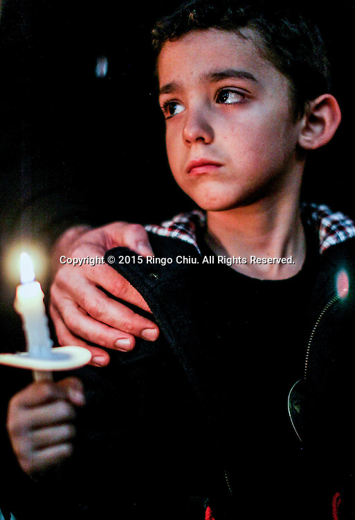 A boy holds a candle light in a memorial service outside Los Angeles City Hall in memory of the victims of Friday's attacks in Paris on November 17, 2015 in Los Angeles.