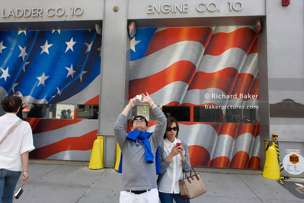 In front of a fire station, visitors use smartphones to record the new One World Trade Center opposite the 9/11 Memorial in New York, killed at the locations of terrorist attacks on September 11th 2001. The National September 11 Memorial is a tribute of remembrance and honor to the nearly 3,000 people killed in the terror attacks of September 11, 2001 at the World Trade Center site, near Shanksville, Pa., and at the Pentagon, as well as the six people killed in the World Trade Center bombing in February 1993.