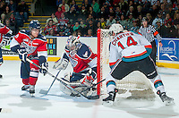 KELOWNA, CANADA - MARCH 28: Eric Comrie #1 of Tri-City Americans makes a save on a wrap around attempt by  Rourke Chartier #14 of Kelowna Rockets  on March 28, 2015 at Prospera Place in Kelowna, British Columbia, Canada.  (Photo by Marissa Baecker/Shoot the Breeze)  *** Local Caption *** Eric Comrie; Rourke Chartier;