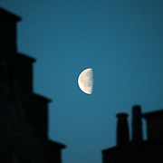 The moon in its third quarter lies in the predawn sky behind chimneys of some of the historic buildings on a street radiating off the Markt in the historic center of Bruges, Belgium.