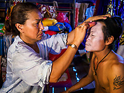 "26 FEBRUARY 2018 - BANGKOK, THAILAND: A performer gets help with his makeup before a Chinese Opera at the Phek Leng Shrine in the Khlong Toey section of Bangkok. The shrine traditionally hosts a Chinese Opera just after the end of Lunar New Year festivities. Thailand is home to the largest population of overseas Chinese in the world, and Chinese cultural practices, like Chinese opera, called ""ngiew"" in Thailand, are popular. Many of the performers are ethnic Thais who don't speak Chinese. They learn their lines phonetically.    PHOTO BY JACK KURTZ"