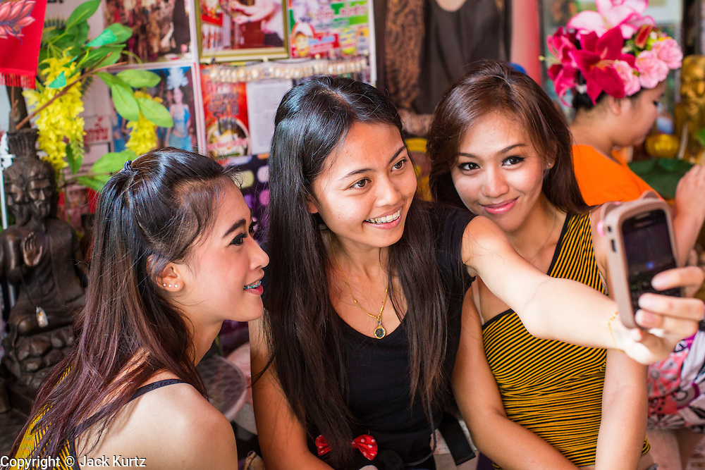 "03 MARCH 2013 - BANGKOK, THAILAND:  NAM (left) and KWANT (right), (stage names) ""coyote dancers"" from the Never Die dance troupe, pose for smart phone photos at the Chuchok Shrine. The Chuchok Shrine is in suburban Bangkok. More than 100 people a week come to the shrine to pray for good fortune or good health. People whose prayers are answered return to the shrine with ""coyote dancers"" to make merit and thank Chuchok. Coyote dancing is a Thai phenomenon created after the US movie ""Coyote Ugly"" where attractive young women dance in a sexually suggestive way, usually for pay. They're common at bars and festivals. Coyote dancers are typically better paid than other Thai women in the hospitality industry and usually are not allowed to date or see customers are off the dance floor. Coyote dancers perform at the Chuchok shrine because according to Buddhist literature Chuchok was a relatively repulsive old hermit and Brahmin priest who was cared for by a young woman after he made her family's wishes come true.  PHOTO BY JACK KURTZ"