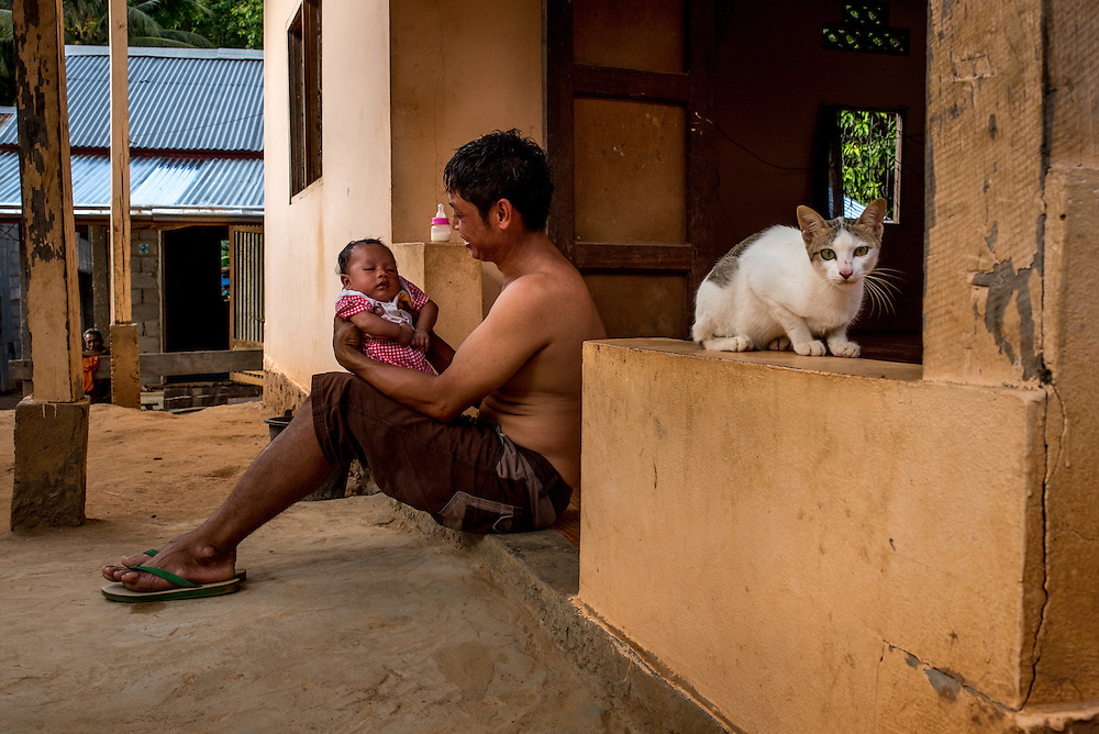 A man with his newborn baby in the village of Khoc Kham. The village is not connected to the main electrical grid and many residents operate their own turbines to power lights and sometimes small appliances.