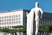 Statue at the Stadio dei Marmi or Stadium of the Marbles, a stadium designed c. 1928 by Enrico Del Debbio and inaugurated 1932, at the Foro Italico, Rome, Italy, and behind, the Palazzo della Farnesina, a government building designed 1935 housing the Ministry of Foreign Affairs. The stadium has Carrara marble steps lined by 59 marble statues of athletes in classical style. The Foro Italico or Foro Mussolini is a sports complex built 1928-38 in Fascist style by Enrico Del Debbio and Luigi Moretti, inspired by Roman forums. Fascist architecture developed in the late 1920s and 1930s, as a modernist style in times of nationalism and totalitarianism under Benito Mussolini. It is characterised by large, square, symmetrical buildings with little or no decoration, often inspired by ancient Rome and designed to convey strength and power. Picture by Manuel Cohen