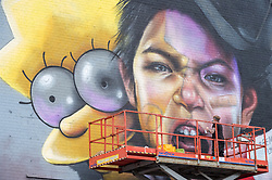 © Licensed to London News Pictures.  27/07/2018; Bristol, UK. Upfest, The Urban Paint Festival, 2018 with themes this year including the Simpsons cartoon series and 100 years of the first women getting the vote. NOMAD CLAN are pictured working on their giant mural with the character of Lisa Simpson on the side of the Tobacco Factory in Bedminster, Bristol. Nomad Clan is possibly the biggest female duo in world street art, having completed the largest mural in the country back in 2017. Their challenge this year is a unique one; to celebrate the suffrage movement with a tie in to The Simpsons using the show's titular post-modern feminist, Lisa Simpson. Upfest which is Europe's largest Street Art and Graffiti Festival takes place in the Bedminster area of Bristol between Saturday the 28th and Monday 30th of July. In celebration of their 10th anniversary, Upfest will feature the animated family, The Simpsons with 2018 festival goers treated to artist interpretations including Homer, Marge, Bart, Lisa, and Maggie. The festival has also teamed up with Bristol Women's Voice to celebrate the centenary of the first votes for women, and together Upfest and Bristol Women's Voice will celebrate the progress made since 1918, with three artists including Nomad Clan chosen to portray the suffrage movement and the rights of women. Upfest will have 400 artists from 70 countries in attendance, including this year's lead artists Insane51, L7m, London Police, Nomad Clan, Odeith, and Paris. This year, three Upfest artists have been selected by The Simpsons creator Matt Groening to bring The Simpsons to life in their own unique styles: Bao, born and based in Hong Kong, is known for her freestyle work with vibrant murals and illustrations; Soker, a wildstyle writer, is one of Bristol's finest talents and has been putting his mark on the city since the late 80's; Nomad Clan, the collective of Cbloxx and AYLO, one of the most sought-after duos in the international global street art scene.