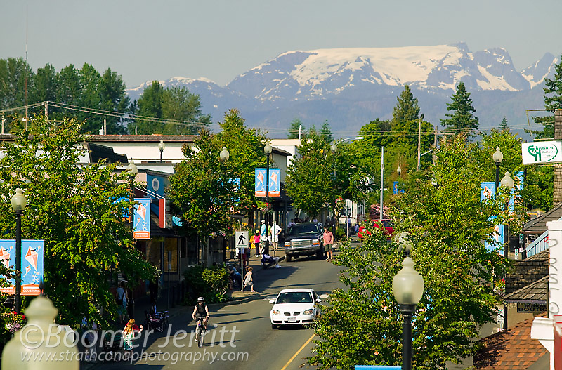 The ever-present Comox Valley Glacier overlooks the main street of downtown Courtenay.  Courtenay, Comox Valley, Vancouver Island, British Columbia, Canada.