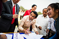 Families arrive at the opening ceremony of the Japanese Encephalitis vaccination campaign in Xieng Khouang province, Laos.