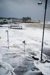 © Licensed to London News Pictures. 06/01/2014. Aberystwyth, UK At either side of the high tide at 11.20am on Monday 06 Jan 2014, a deep depression drives a huge ground swell of waves to crash into the promenade at Aberystwyh, already partly destroyed by the storms of the past three days. Earlier Police and local authority officers had been going house to house on Aberystwyth promenade strongly advising ALL residents to evacuate their seafront properties immediately, in advance of these potentially very damaging set of high waves.  Photo credit : Keith Morris/LNP