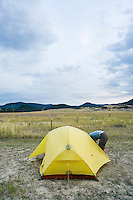 Camper bending over to get in a tent.  Southwest Montana near Fairview Hot Springs.