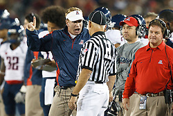 November 6, 2010; Stanford, CA, USA;  Arizona Wildcats head coach Mike Stoops argues with head linesman Jeff Hansen on the sidelines against the Stanford Cardinal during the second quarter at Stanford Stadium. Stanford defeated Arizona 42-17.