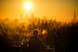 © Licensed to London News Pictures. 29/12/2016. London, UK. A man and his children stop on Parliament Hill on Hampstead Heath London to watch the sunrise over the city of London on another cold winter morning. Most of the UK has woken to freezing temperatures. Photo credit: Ben Cawthra/LNP