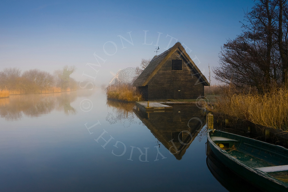 Thatched boathouse on the River Ant, Ludham, Norfolk Broads N.P. Misty winter morning. Windpump in distance.
