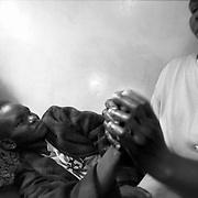 HIV sufferer, Jael Achieng Onunga, receives a hand massage from KICOSHEP (Kibera Community Self Help Program) home care provider Pariks Akinyi at Jael's home in Rongai, Kenya.