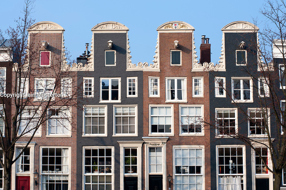 Traditional historic Dutch gable houses beside  canal in Amsterdam The Netherlands