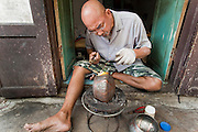 "Mar. 21, 2009 -- BANGKOK, THAILAND:    A man handcrafts a monk's bowl on Soi Baan Bat. The bowls are made from eight separate pieces of metal said to represent the Buddha's Eightfold Path. The Monk's Bowl Village on Soi Ban Baat in Bangkok is the only surviving one of what were originally three artisan's communities established by Thai King Rama I for the purpose of handcrafting ""baat"" the ceremonial bowls used by monks as they collect their morning alms. Most monks now use cheaper factory made bowls and the old tradition is dying out. Only six or seven families on Soi Ban Baat still make the bowls by hand. Most of the bowls are now sold to tourists who find their way to hidden alleys in old Bangkok. The small family workshops are only a part of the ""Monk's Bowl Village."" It is also a thriving residential community of narrow alleyways and sidewalks.     Photo by Jack Kurtz"