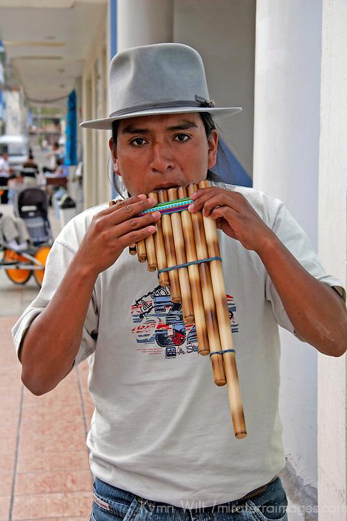South America, Ecuador, San Anotnio de Ibarra.  A local Ecuadorian plays the panflute, a traditional instrument of the Andes.