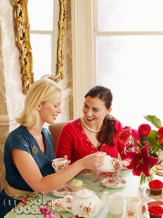 Two young women sitting at dining table pouring tea elevated view